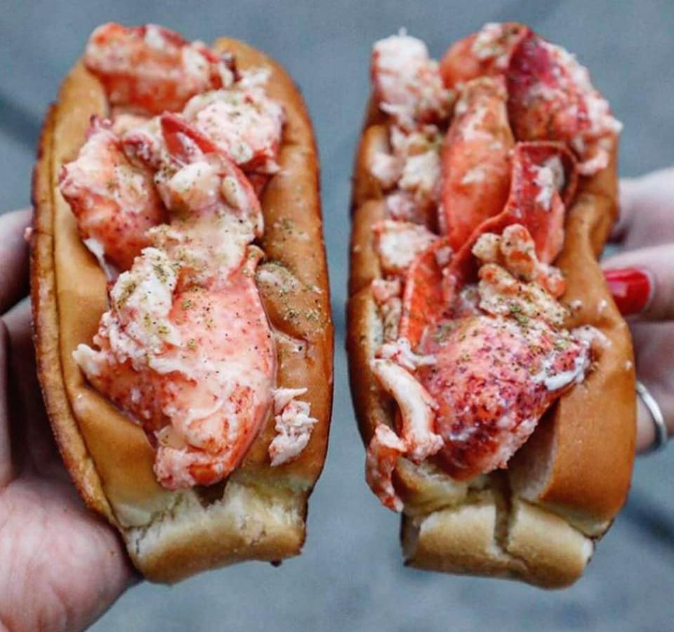 Two lobster rolls from Luke's, held in front of camera