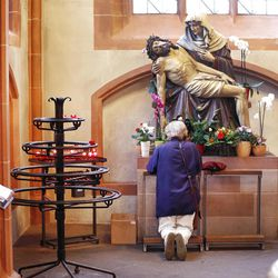 A woman prays under a statue depicting Jesus and Mary, in the cathedral of Frankfurt, Germany. German Catholics who don't pay religious taxes can be denied sacraments.