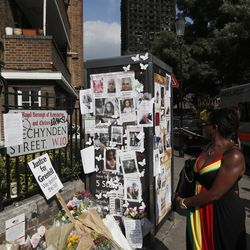 A woman looks towards missing posters stuck on a phone box in front of the remains of Grenfell Tower in London, Saturday, June 17, 2017.  Police Commander Stuart Cundy said Saturday  it will take weeks or longer to recover and identify all the dead in the public housing block that was devastated by a fire early Wednesday.