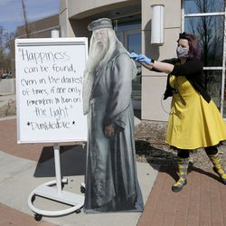 """Children's librarian Lauren Tolman, dressed as a Hufflepuff from """"Harry Potter,"""" adjusts a cardboard cutout of Dumbledore to stop it from falling over in the wind outside of the Springville Library in Springville on Wednesday, April 8, 2020."""