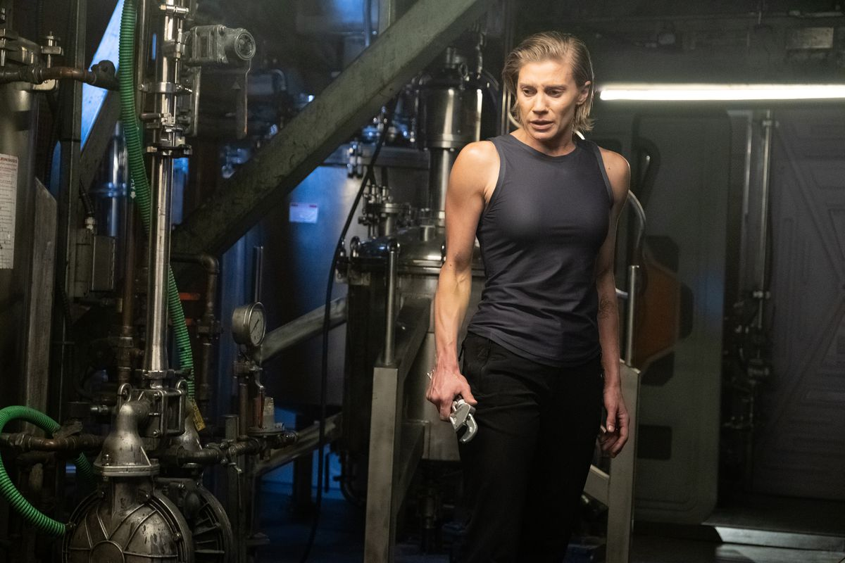 A production still from Another Life showing Katie Sackhoff holding a wrench in the engineering area of a space ship.