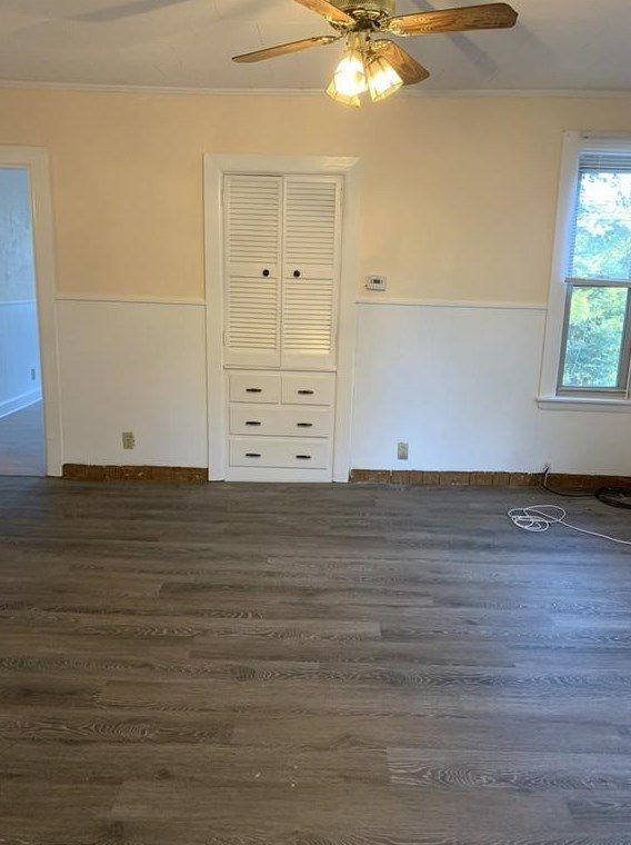 An empty room with a ceiling fan and a cabinet.