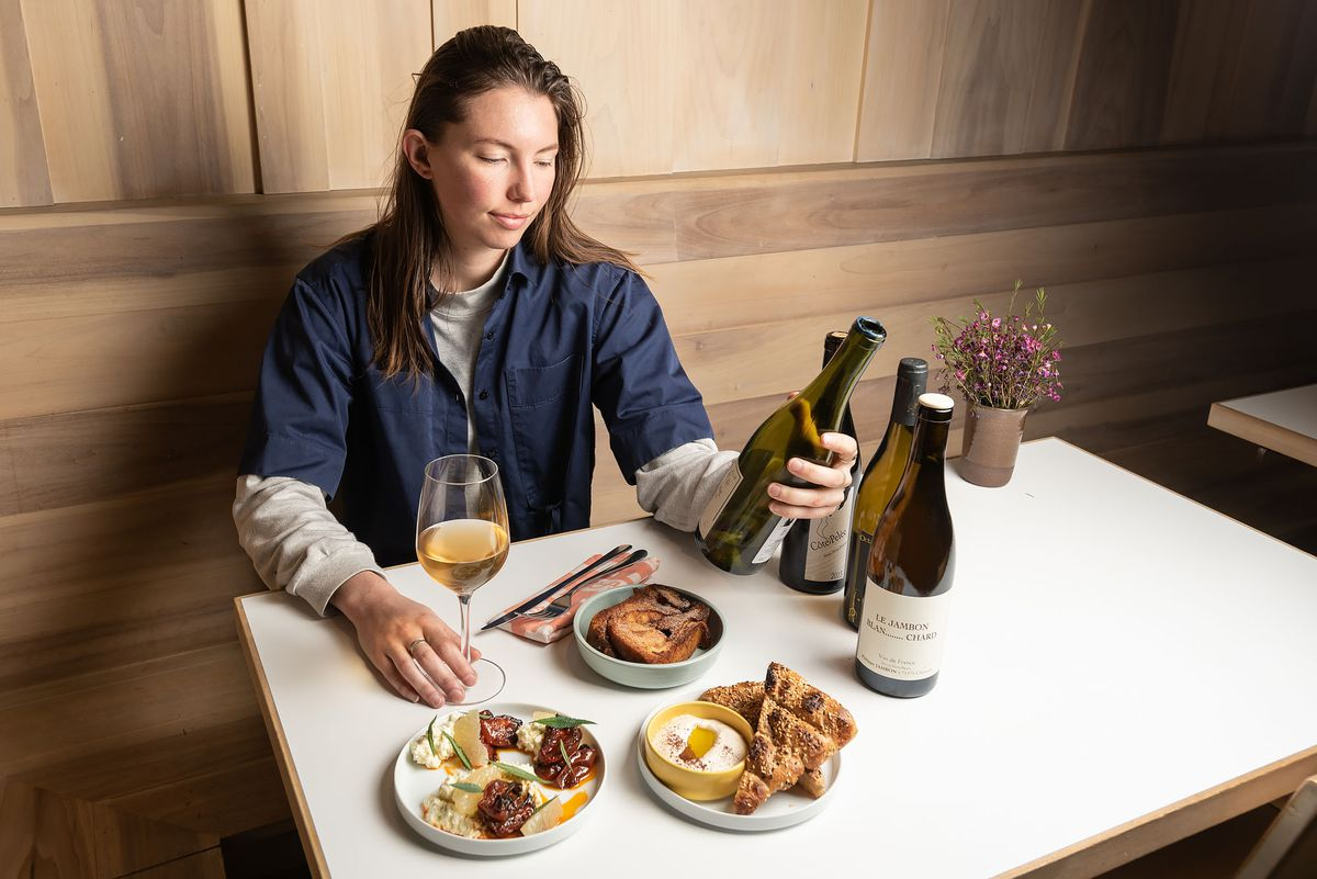 Kae Whalen sits at a table with food and wine bottles at Kismet.
