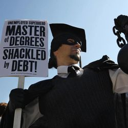 """In this Oct. 6, 2011, file photo, Gan Golan, of Los Angeles, dressed as the """"Master of Degrees,"""" holds a ball and chain representing his college loan debt, during Occupy DC activities in Washington."""