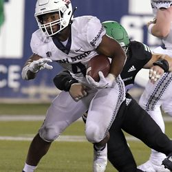 Utah State running back Calvin Tyler Jr. (4) carries the ball as North Dakota linebacker Quinton Urwiler defends during the first half of an NCAA college football game Friday, Sept. 10, 2021, in Logan, Utah.