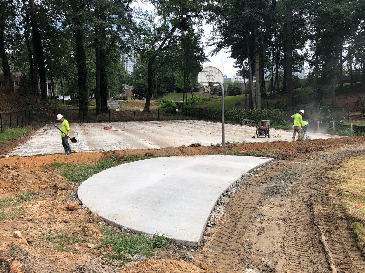 Construction photo of basketball court with goal.