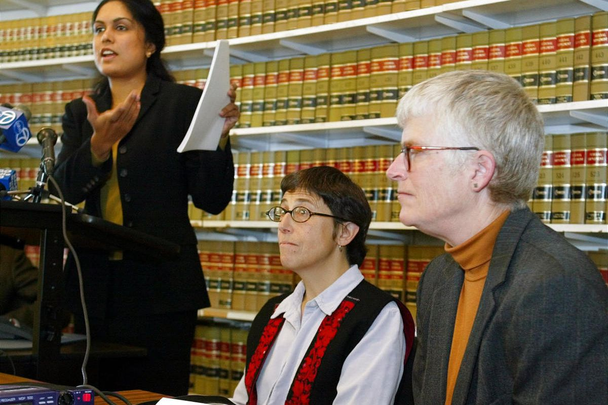 ACLU attorney Jayashri Srikantiah, left, holds up copies of records showing passengers checked on no-fly lists from San Francisco International Airport, as plaintiffs Jan Adams, right, and Rebecca Gordon, center, look on.