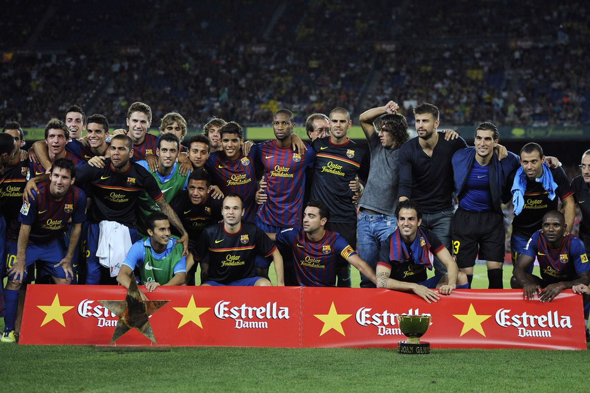 Cesc seems to be enjoying himself sitting behind another trophy.