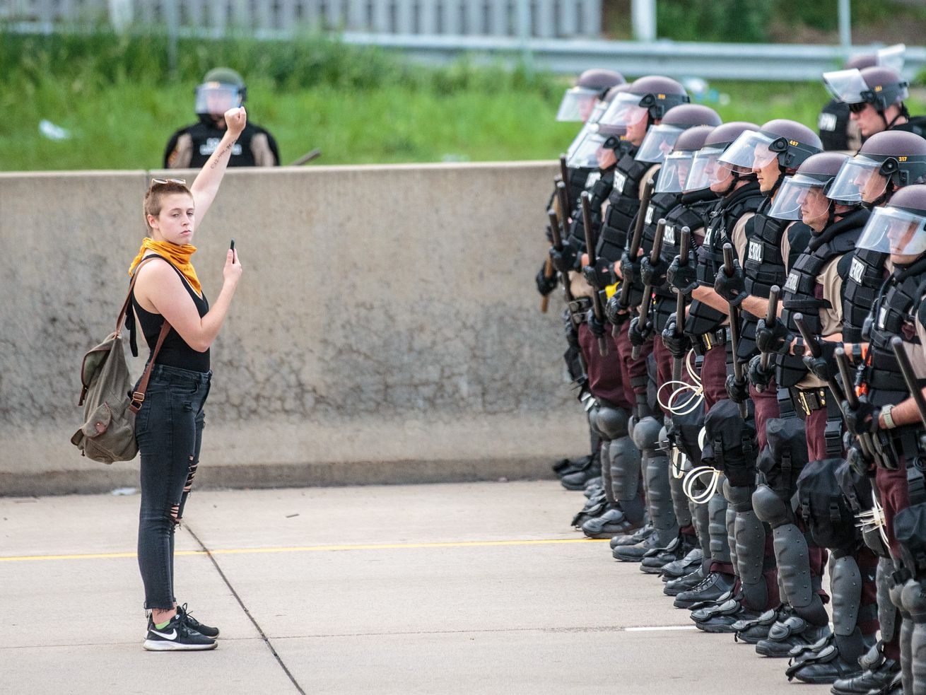 A woman stands in front of a line of Minnesota police.