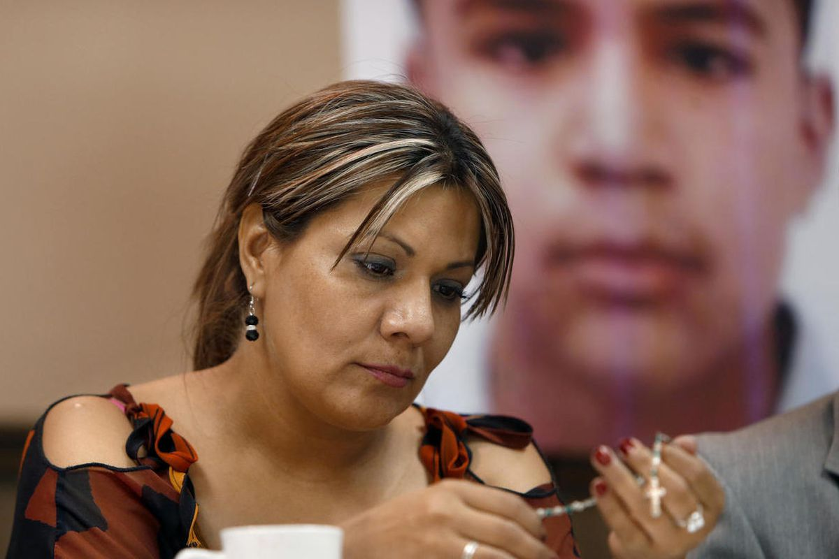 FILE - In this July 29, 2014, file photo, Araceli Rodriguez handles a rosary that belonged to her son Jose Antonio Elena Rodriguez, pictured behind her, who was shot and killed by U.S. Border Patrol agent in October 2012, during a news conference in Nogal