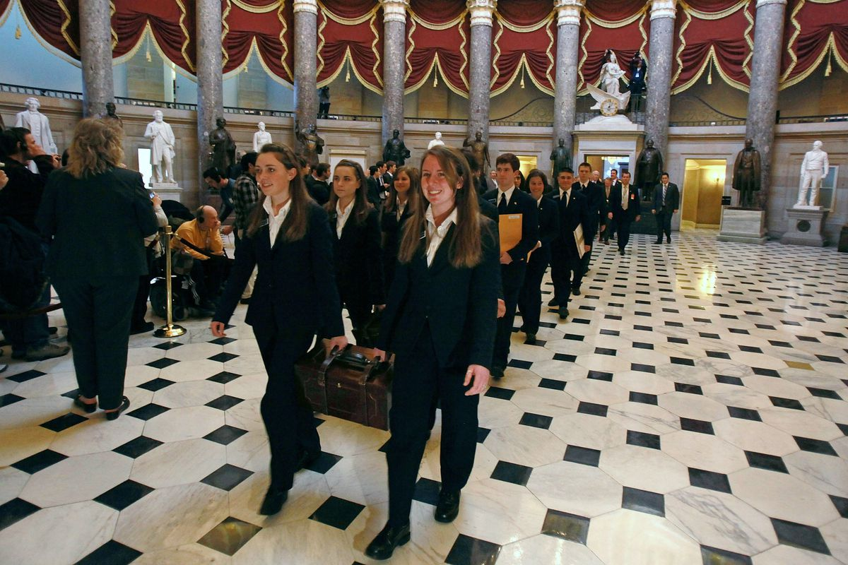 US Senate Pages carry ballot boxes through Statuary Hall toward the House Chamber so electoral votes can be counted.