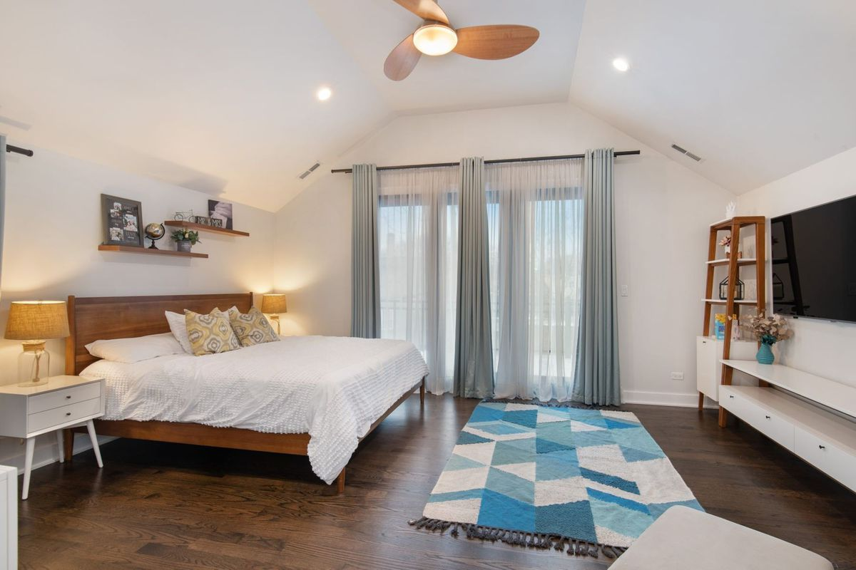 The master bedroom has a vaulted ceiling, a bed, large windows, and two nightstands with lamps.