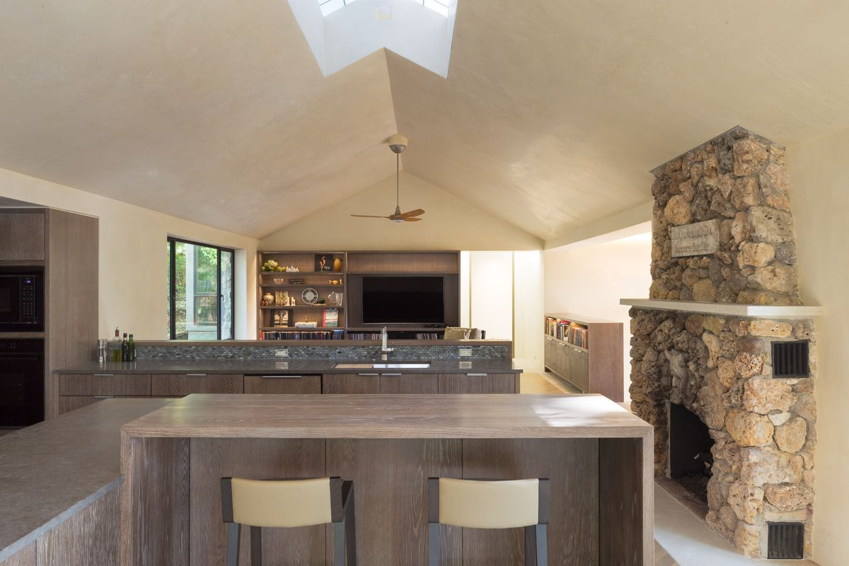 Interior contemporary home with tranditional stone fireplace, peaked roof with skyling, brown and tan furniture