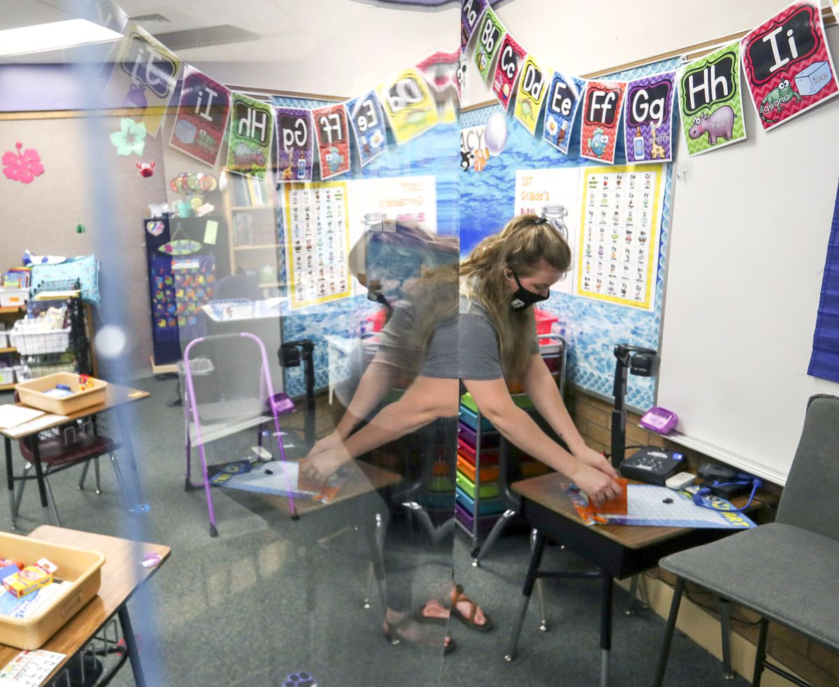 First grade teacher Jamie Greenwood is reflected in a large sheet of clear plastic that hangs from the ceiling as she organizes her classroom at Westvale Elementary School in West Jordan on Wednesday, Aug. 19, 2020. Greenwood will stand behind the plastic when she teaches her class. The Jordan Board of Education will appropriate $500 to each classroom teacher for personal protective equipment and supplies.