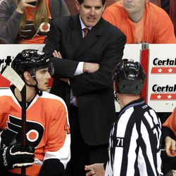 Philadelphia Flyers head coach Peter Laviolette , rear, talks to linesmann Brad Kovachik, right, during a break in the action of the third period of Game 3 in a first-round NHL Stanley Cup playoffs hockey series with the Pittsburgh Penguins Sunday, April 15, 2012, in Philadelphia. The Flyers' 8-4 win puts them ahead 3-0 in the series. (AP Photo/Tom Mihalek)
