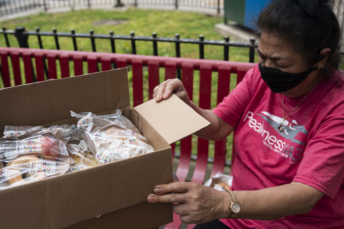 Carmen examines a box of food she collected from the base of her building at the Baruch Houses, May 29, 2020.