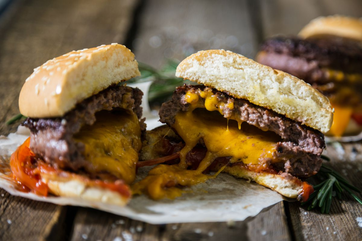 A jucy lucy burger cut in half with cheddar cheese baked into the meat