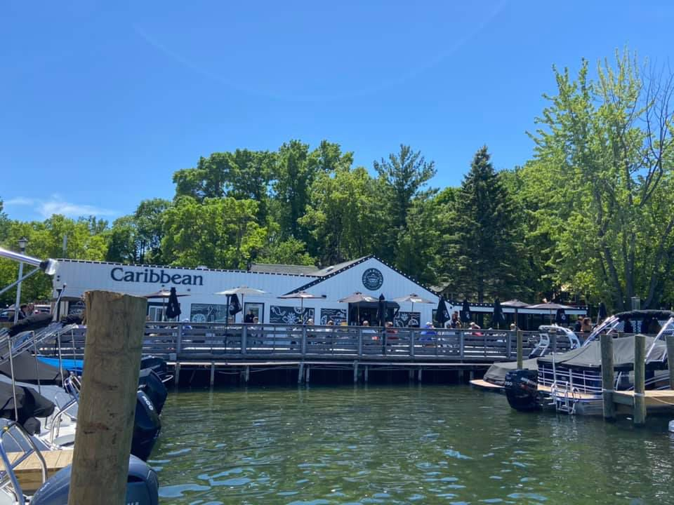 The view from the lake with docking space to the Tequila Butcher at The Caribbean. The building is white with a black roof. A few outdoor tables with umbrellas are visible.