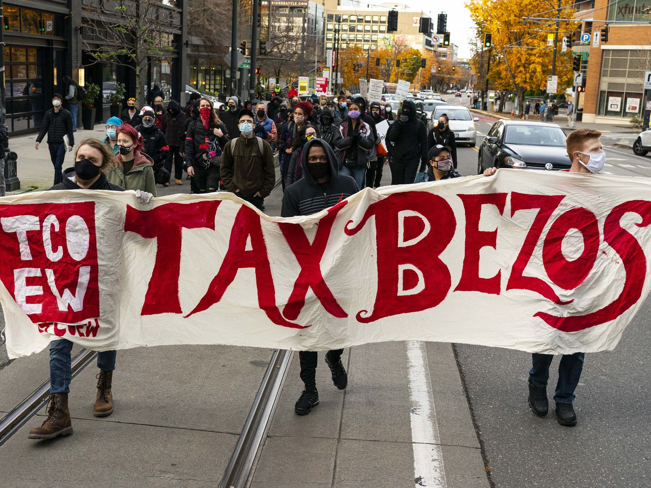 "Demonstrators protest outside Amazon headquarters, holding a sign reading ""Tax Bezos""."