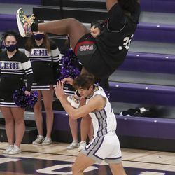 Bountiful's Rob Whaley hangs on the rim after missing a dunk during a game at Lehi High School on Friday, Dec. 11, 2020.