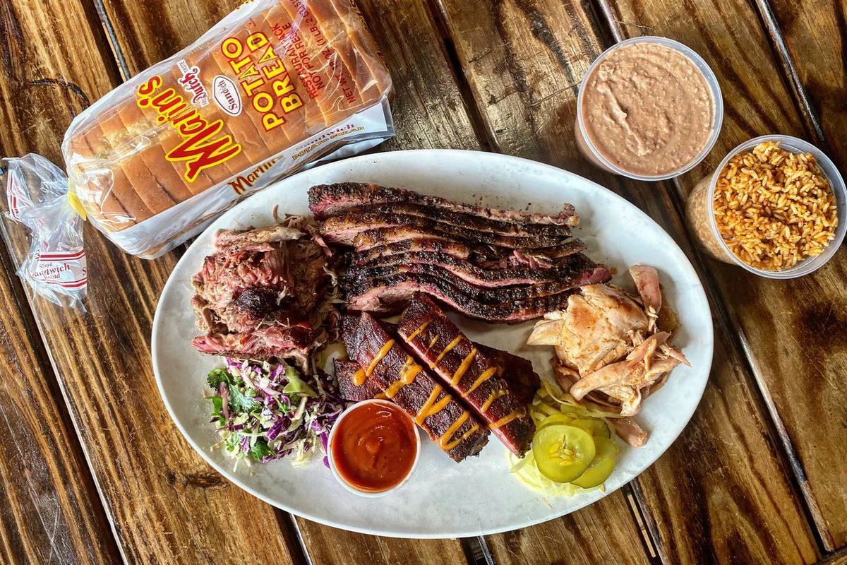 A white plate with barbecue meats and sauces on a wooden table next to a plastic bag of sliced bread and a container of bean dip and another container of rice