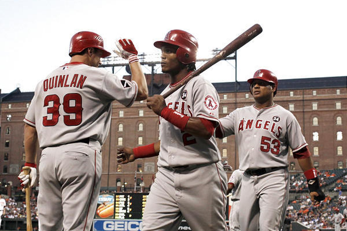Los Angeles Angels' Erick Aybar (2) and Bobby Abreu (53) celebrate with teammate Robb Quinlan (39) after Aybar and Abreu both scored on a single hit by Juan Rivera.