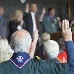 """A man gives the Scout salute while the audience sings """"On My Honor"""" at the dedication of the Thomas S. Monson Lodge at the Hinckley Scout Ranch in the Uinta Mountains on Wednesday, Oct. 5, 2016."""