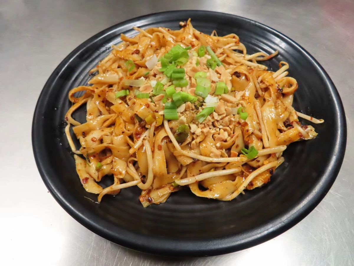 A plate of stir-fried noodles, garnished with chopped scallions