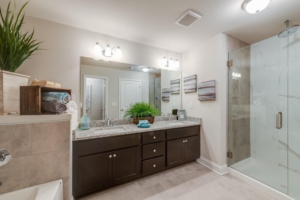 A big white master bathroom with a glass shower.