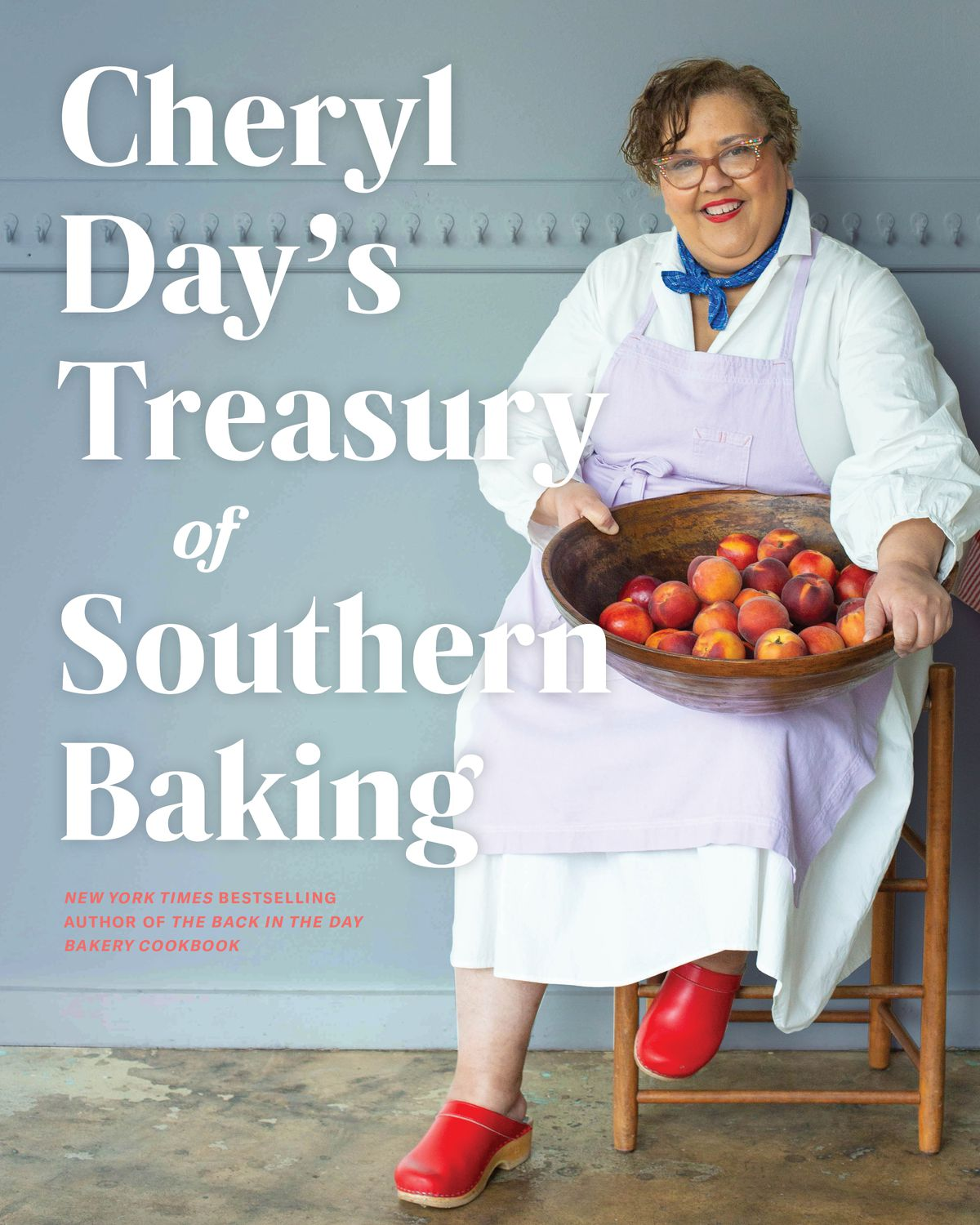 A woman, Cheryl Day, sits in a chair holding a large bowl of peaches on the cover of Cheryl Day's Treasury of Southern Baking