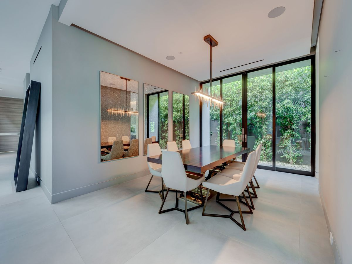 A dining room with a dining set and floor-to-ceiling windows overlooking greenery.