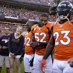 Olympic gold medalist Missy Franklin, second from left, laughs while in the coin toss huddle with the Denver Broncos and the Pittsburgh Steelers  players before their NFL football game, Sunday, Sept. 9, 2012, in Denver.