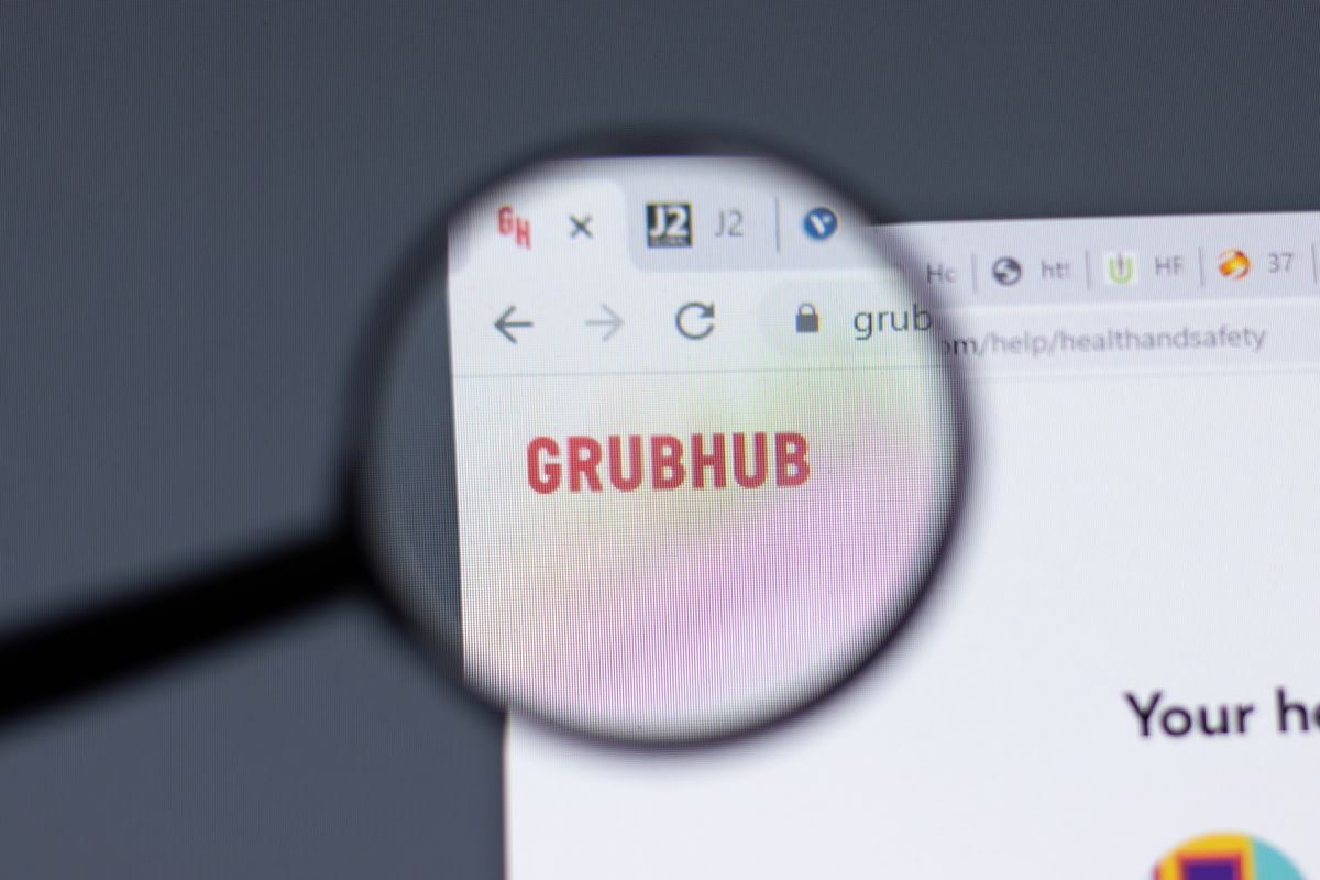 """A magnifying glass over the word """"Grubhub"""" on a computer screen."""