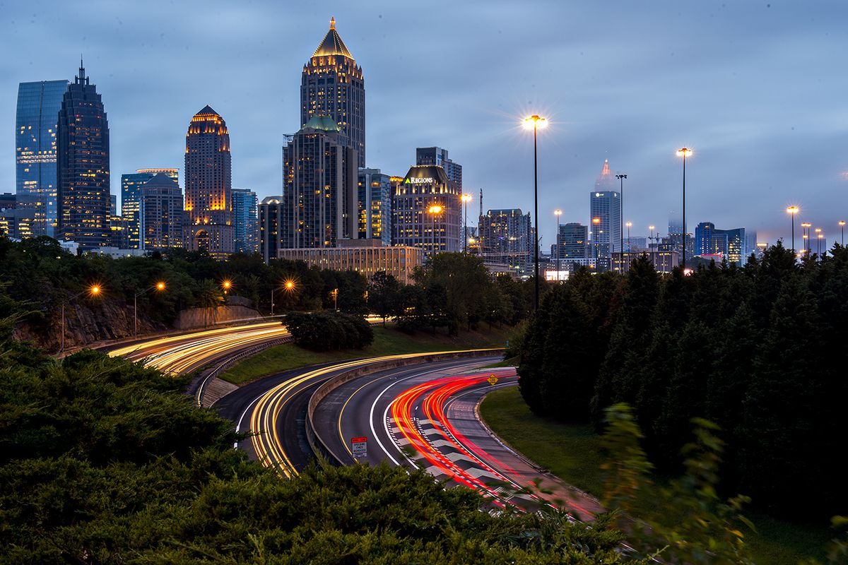 A scene of blurred traffic and many high-rises against a blue sky in Atlanta.
