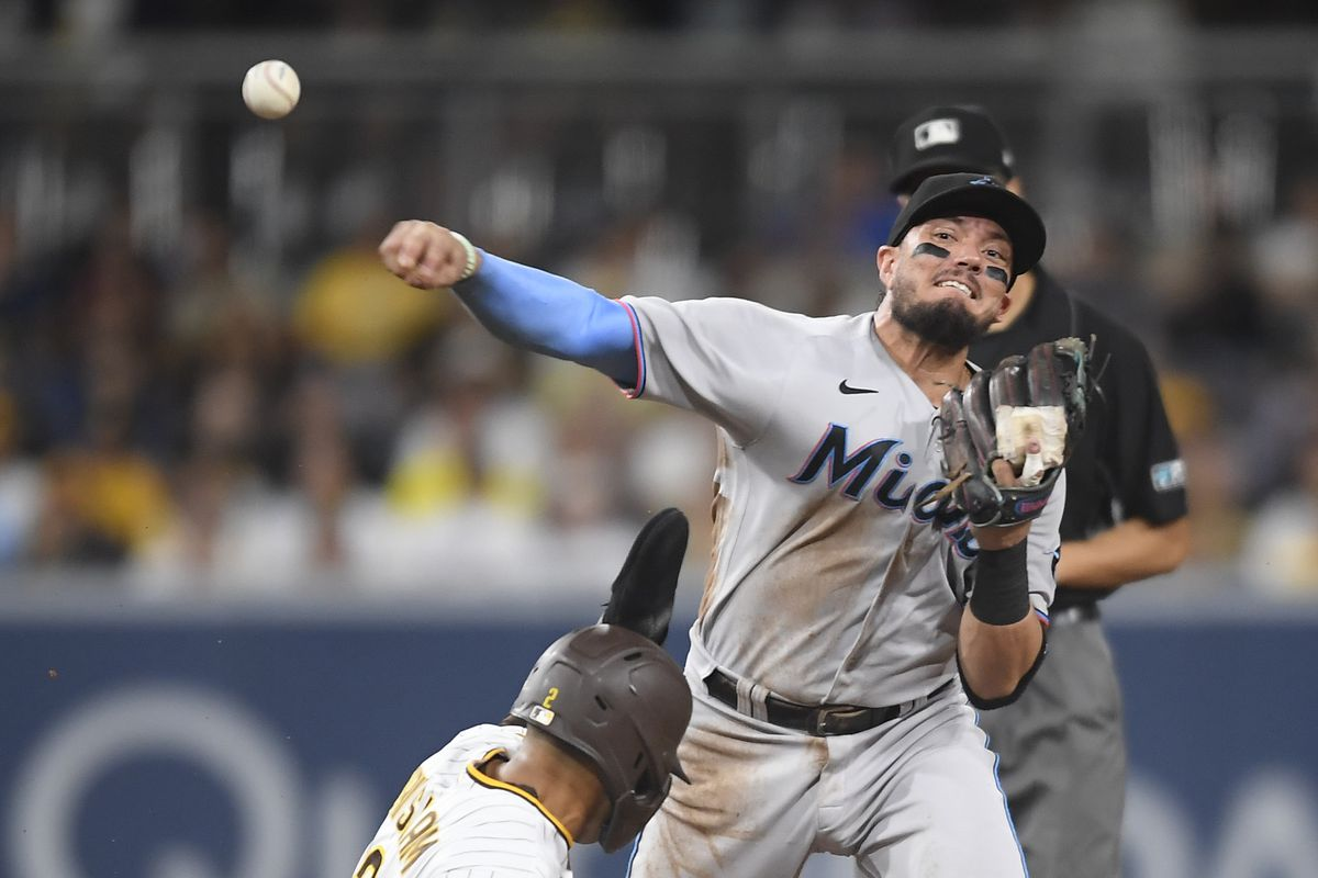 Miguel Rojas #19 of the Miami Marlins throws over Trent Grisham #2 of the San Diego Padres as he turns a double play during the second inning of a baseball game at Petco Park