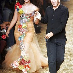 This Oct. 4, 2005 file photo shows French fashion designer Jean-Paul Gaultier taking the catwalk with model Crystal Renn at the end of the presentation of his Spring/Summer ready to wear 2006 collection, in Paris.