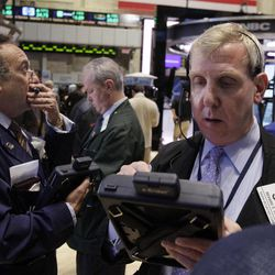 Richard Cohen, right, works with fellow traders on the floor of the New York Stock Exchange, Monday, April 16, 2012, in New York. The Dow Jones industrial average rose but other stock indexes fell early Monday as a strong report on retail sales didn't dispel worries about the economy.