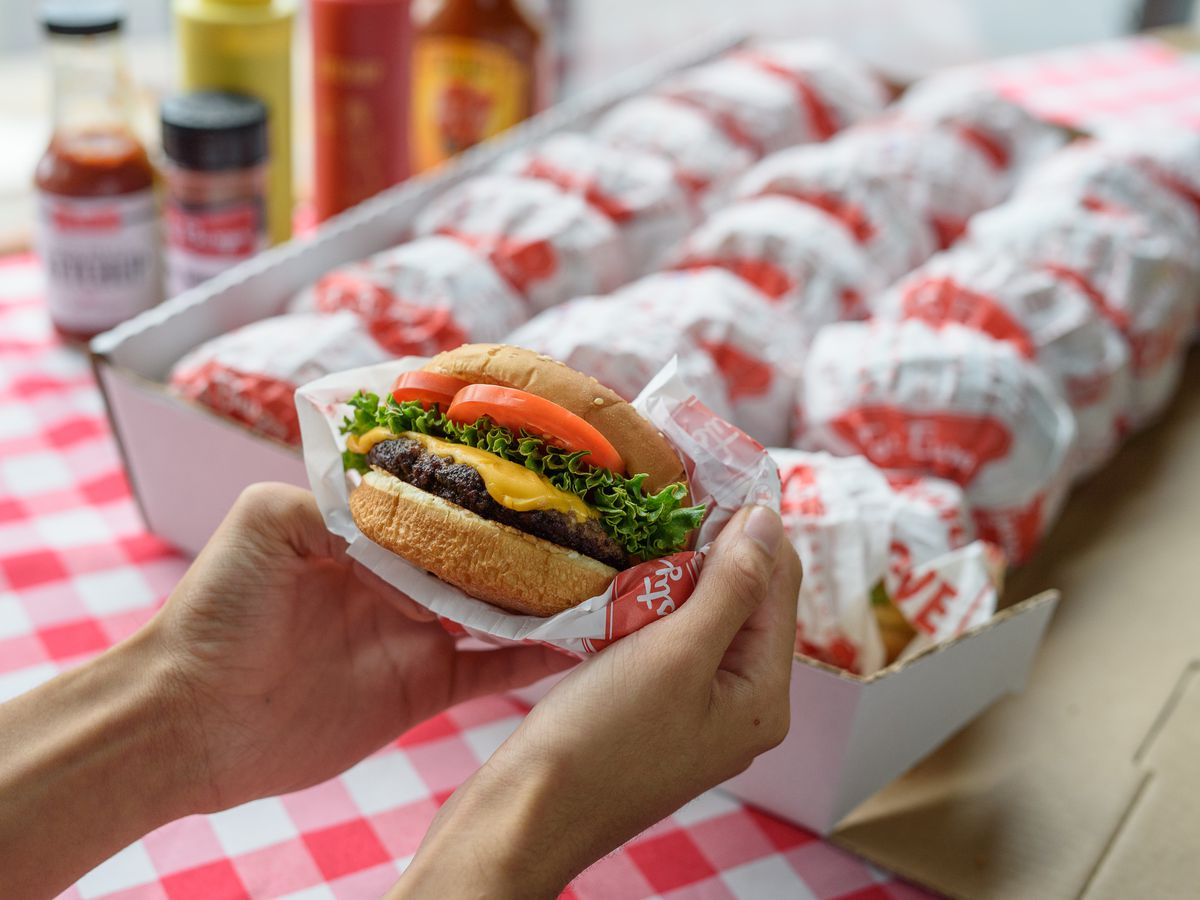 Two hands hold a fast-food burger in front of a box full of more burgers, all over a red checkered tablecloth.