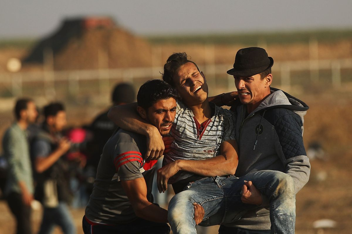 An injured protester is carried to an ambulance at the border fence with Israel on May 15, in Gaza City, Gaza.