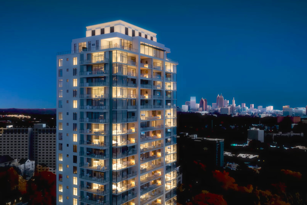 A condo tower with large balconies looking toward a city in the distance.