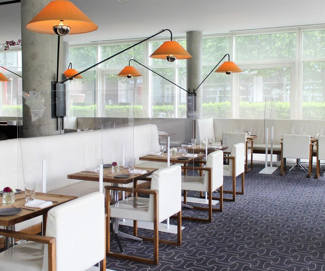 White chairs are arranged for service in a restaurant with views of a courtyard garden visible through partially opaque windows