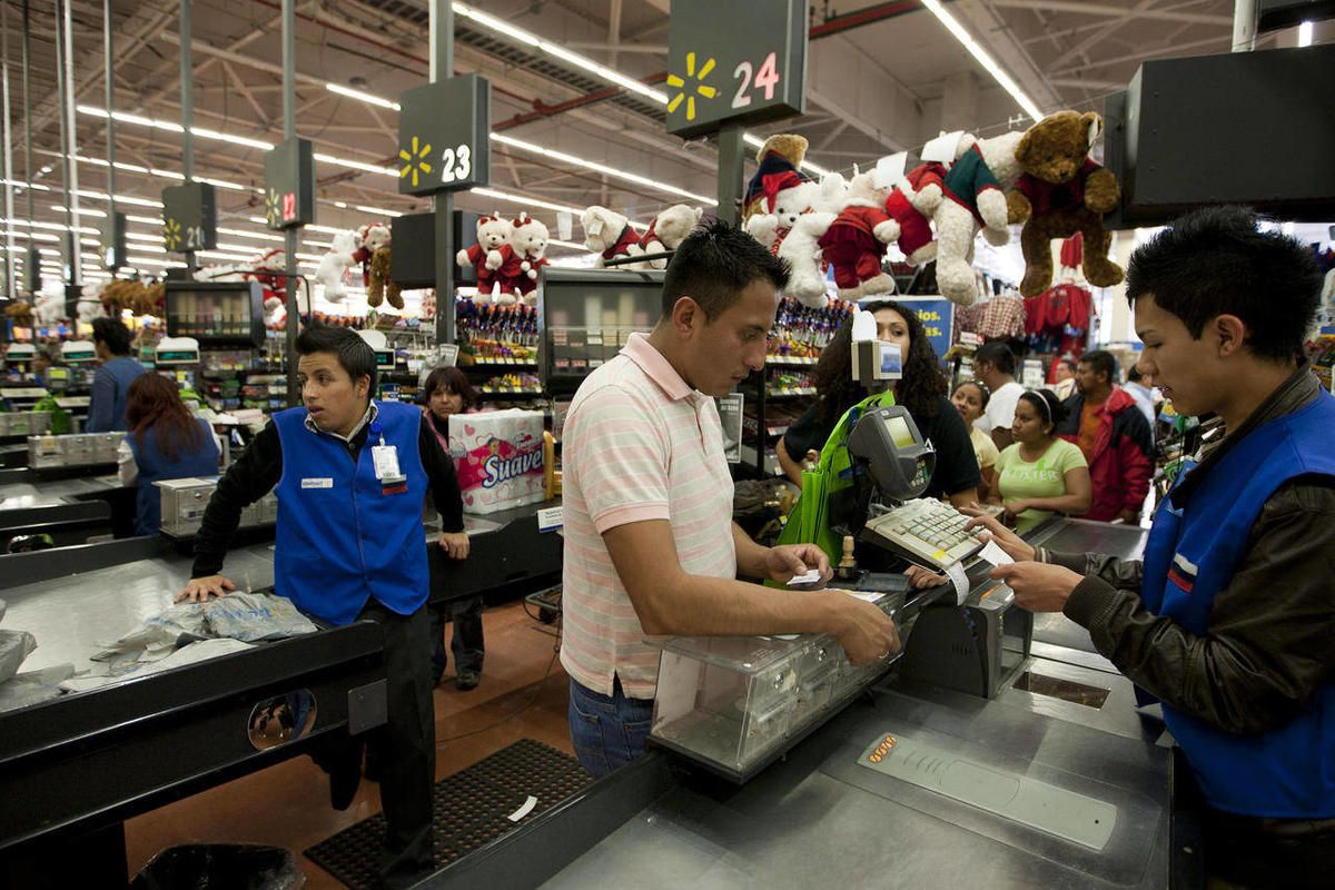 In this Nov. 18, 2011 photo, a man pays at the cash register at a Wal-Mart Superstore in Mexico City. Wal-Mart Stores Inc. hushed up a vast bribery campaign that top executives of its Mexican subsidiary carried out to build stores across Mexico, according