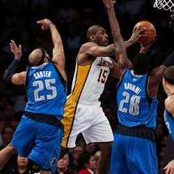 Los Angeles Lakers forward Metta World Peace, middle, attempts a shot over  Mavericks center Ian Mahinmi, right, and guard Vince Carter, left, during the first half of an NBA basketball game, Sunday, April 15, 2012, in Los Angeles.
