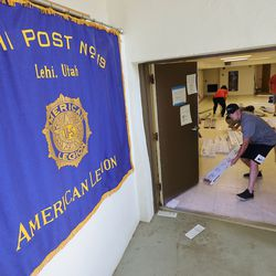 """Ken Garff volunteers install flooring as part of a three-day makeover project at Lehi American Legion Post No. 19 in Lehi on Tuesday, June 22, 2021. The project is part of Ken Garff's """"We're 'Hear' for You"""" initiative that is committed to reaching out to community groups and organizations and help them recover from the effects of the pandemic."""
