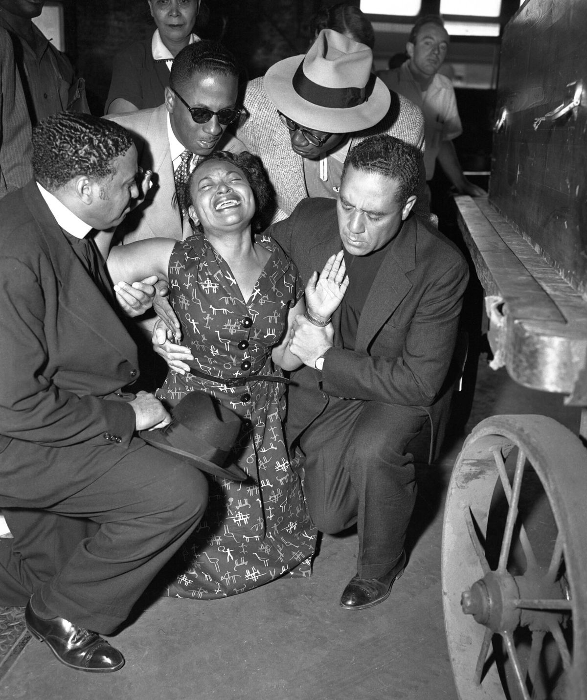 Mamie Till Mobley collapses as her son Emmett Till's body arrives at Chicago's old Illinois Central Railroad station after his murder by racists in Mississippi. On her left, with the white collar, is Alva Doris Roberts' husband, Bishop Isaiah L. Roberts, who presided over the funeral. On the right, also dressed in clerical black, is Bishop Louis Henry Ford, who gave the eulogy for the slain teenager.