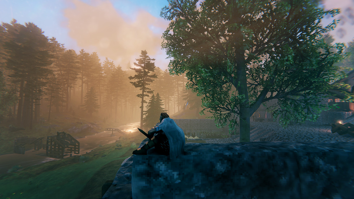 Viking sits on a wall admiring the landscape. Screen image from the Valheim