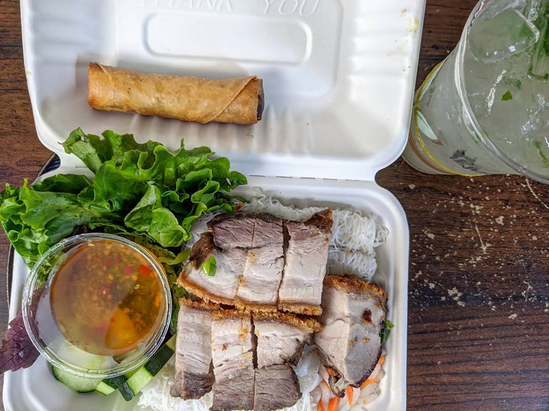 A white takeout container is filled with a Vietnamese dish of vermicelli noodles packed in squares, topped with crispy pork belly, herbs, and cucumbers. There's an egg roll and a plastic cup of limeade on the side.