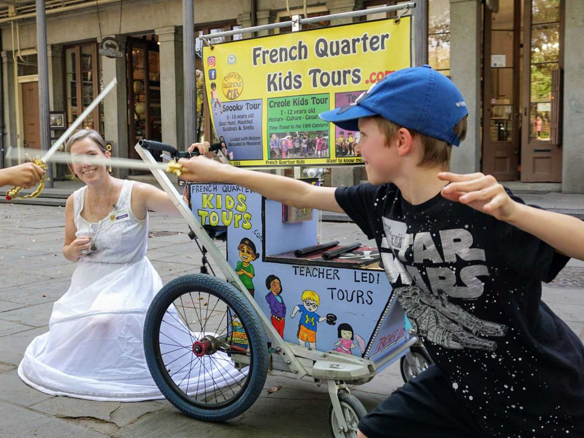 Children play with toy swords on a street. There is a sign on a building in the background that reads: French Quarter Kids Tours.