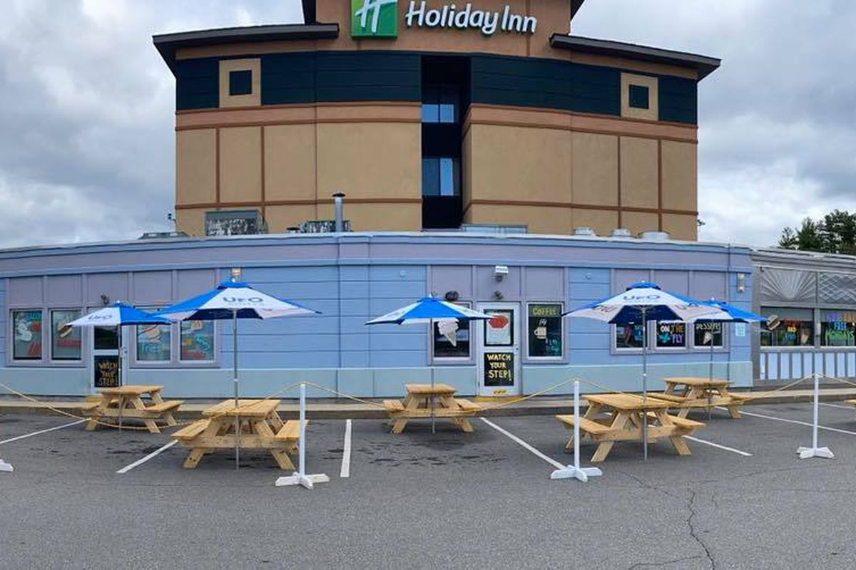 Empty picnic tables, each with a blue and white umbrella, are spread across a parking lot in front of a restaurant. A Holiday Inn is visible right behind the restaurant.