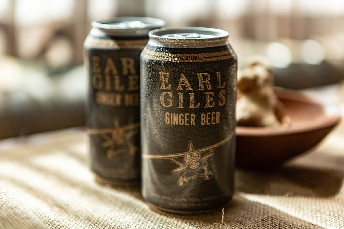 Two dark colored cans of Earl Giles with just a little cold condensation on the cans